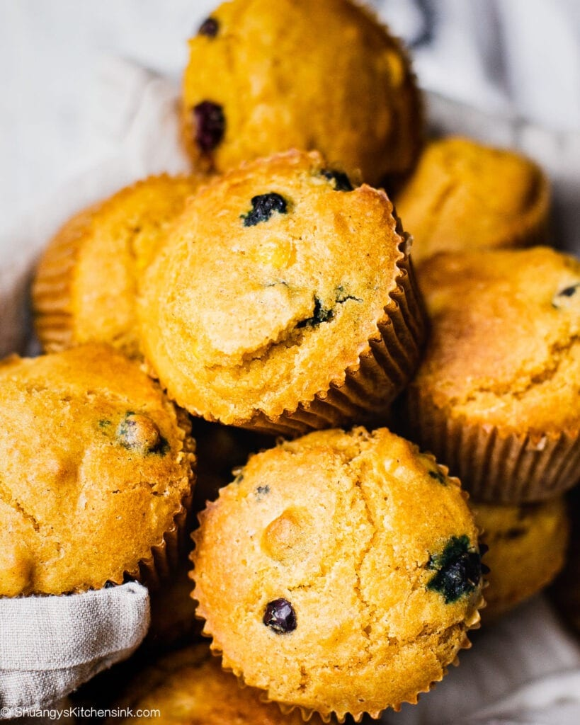 A close up picture of a basket full of freshly baked blueberry cornbread muffins
