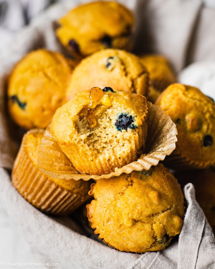 There are many cornbread muffins. Someone has taken a bite from he one in the front. There is honey drizzled on the dessert