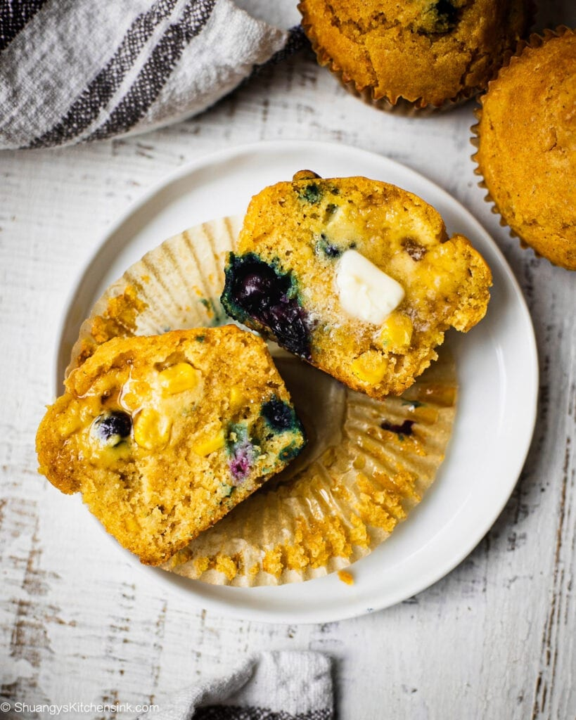 A muffin cut in half. You can see juicy blueberries and pieces of corn inside of it. These is honey and vegan butter on top of the dessert