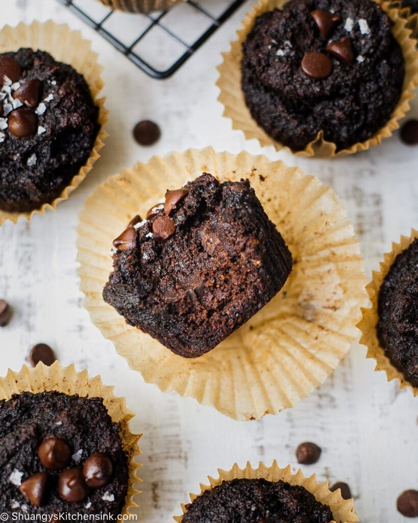 The picture is centered around a healthy chocolate muffin on a muffin paper. Someone has taken a bite from it. Around this muffin there are found other, untouched muffins