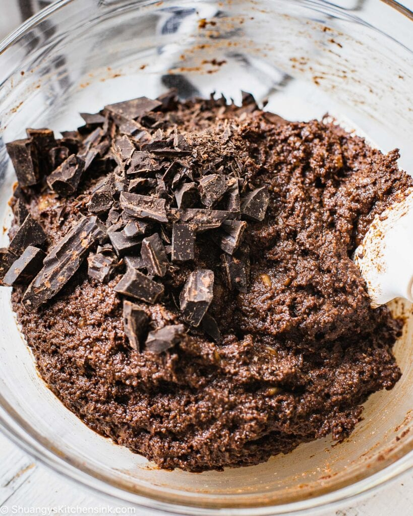 Chocolate muffin batter with chunks of dark vegan chocolate being folded into it.