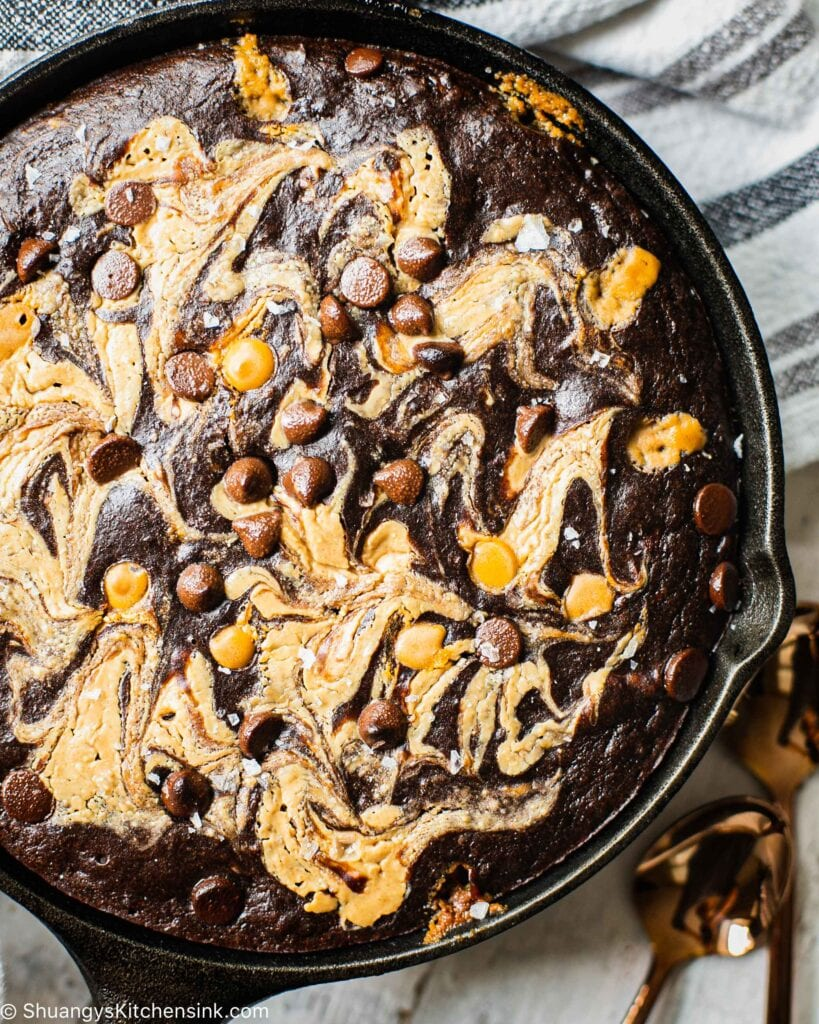 a freshly baked chocolate cake made in a cast iron pan . it's drizzles with nut butter and sprinkled with chocolate chips and sea salt