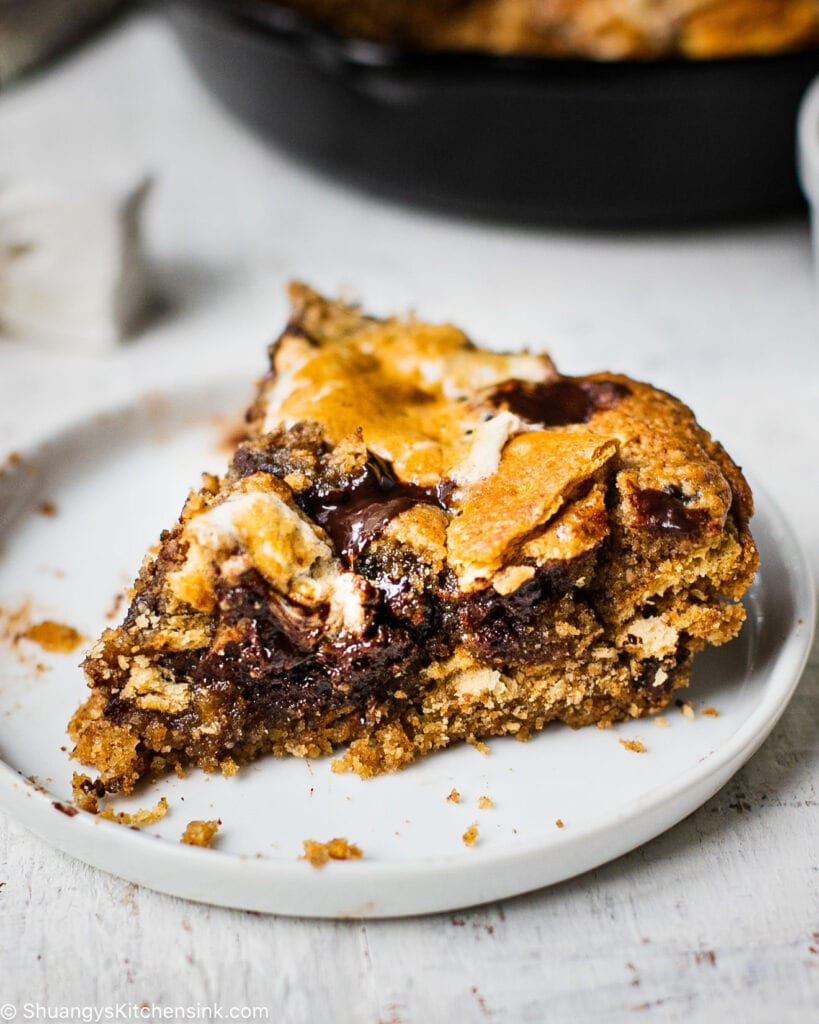 A big piece of a ooey gooey chocolate filled s'mores cookie cake that has sticky marshmallows and graham crackers on top