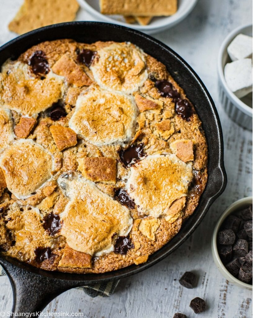 On a gray table there is a cast iron skillet with a big s'more cookie in it. You can see caramelized marshmallows and melted chocolate on top of the paleo cookie