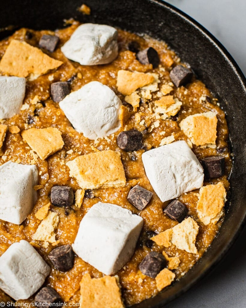 a cast iron pan filled with a cake batter and topped with marshmallows, gluten free graham crackers and vegan chocolate chips. The cake has not been baked yet.