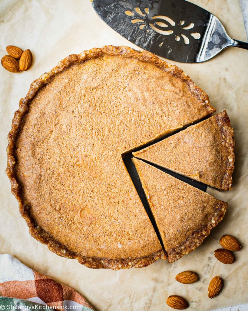 two pieces are cut from a pie . There are raw almonds on the side