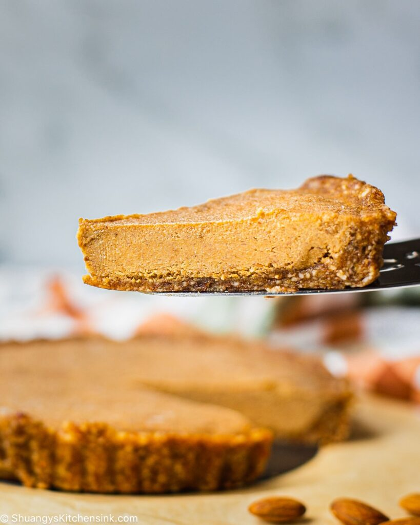 A piece of pumpkin cheesecake is being held up on a cake server. the whole pie is seen in the background