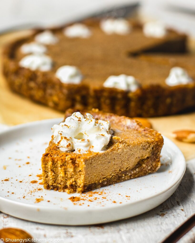 A piece of pumpkin pie cheesecake that someone has taken a bite from. The pie is topped with dairy free whipped cream