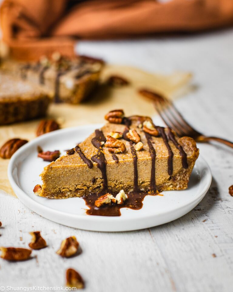 There is a piece of no bake pumpkin cheesecake on a round plate. It's drizzles with homemade chocolate ganache and walnuts are sprinkled on top
