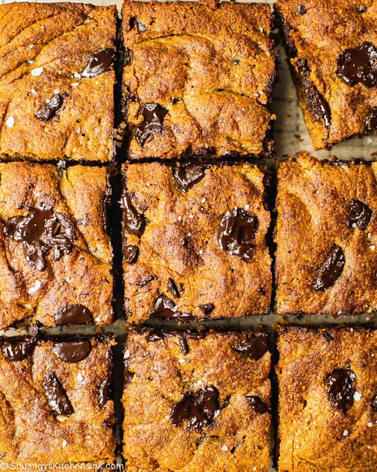 A pan of freshly baked pumpkin pie chocolate chip cookie bars on a cutting board. The healthy bread has been cut into nine squares.