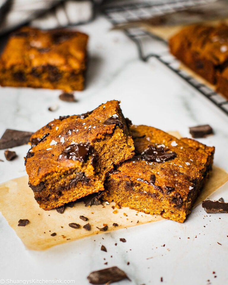 two pieces of healthy pumpkin cookie bars stuffed with rich and melted chocolate. There are sprinkles of sea salt on top. The rest of the pumpkin loaf is in the background as well.