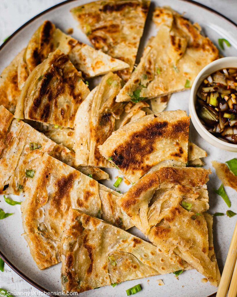 A Chinese Scallion Pancake cut into smaller wedges. There is a pipping sauce on the side and chopsticks.