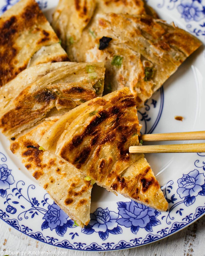 A pair of chopsticks are grabbing a piece of homemade flat bread from a white and blue plate