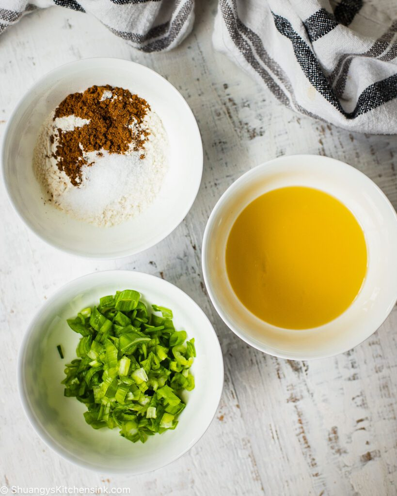 three bowls on a table. One with scallions, one with hot oil and one with a five-spice blend