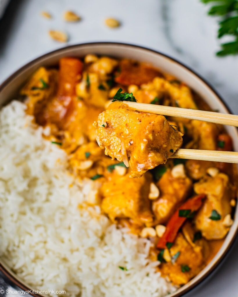 A pair of chopsticks are grabbing a piece of chicken from a bowl full of rice, and Thai peanut curry