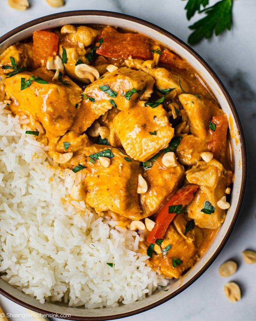 A bowl with Jasmine rice and juicy tender chicken covered in a creamy sauce. There are also red peppers, peanuts and fresh cilantro