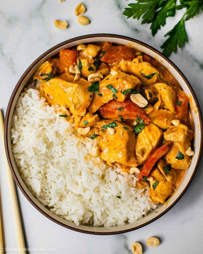 A bowl filled with rice and spicy peanut butter chicken curry. There are red bell peppers in the bowl as well. The healthy dish is sprinkled with peanuts and fresh cilantro. There are chop sticks on the side