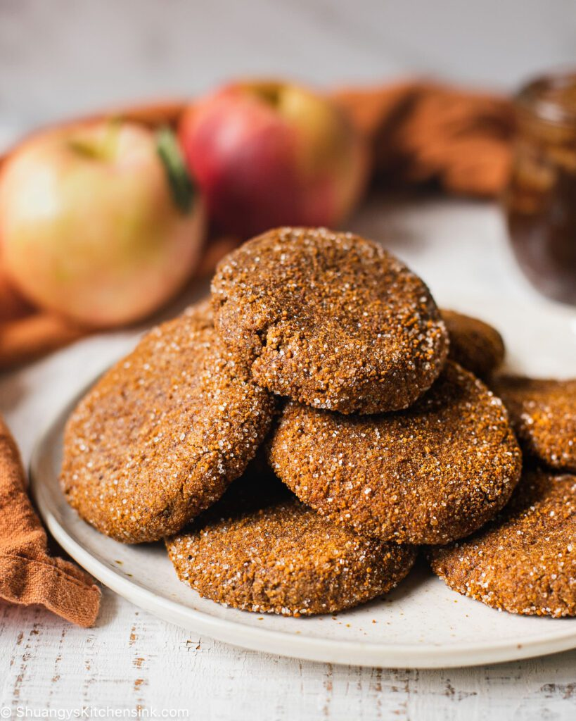 a plate of healthy and gluten-free cookies. There are apples in the background