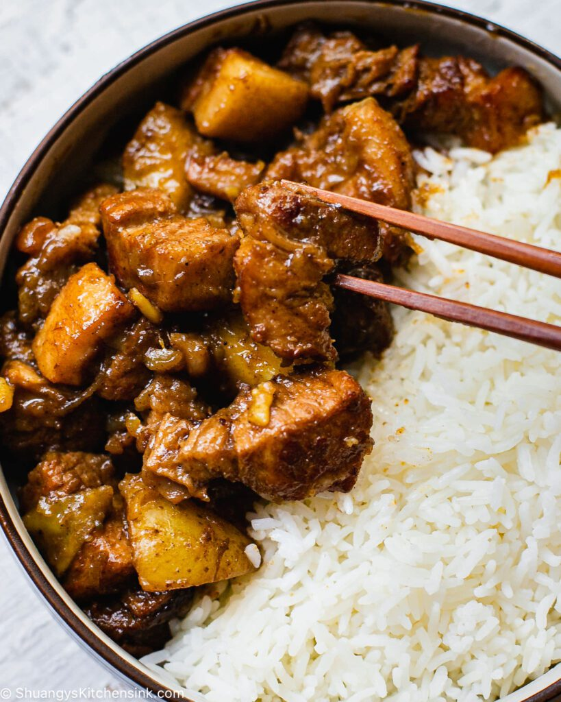 A bowl with braised pork belly and while jasmine rice. a pair of chopsticks are about to dig in