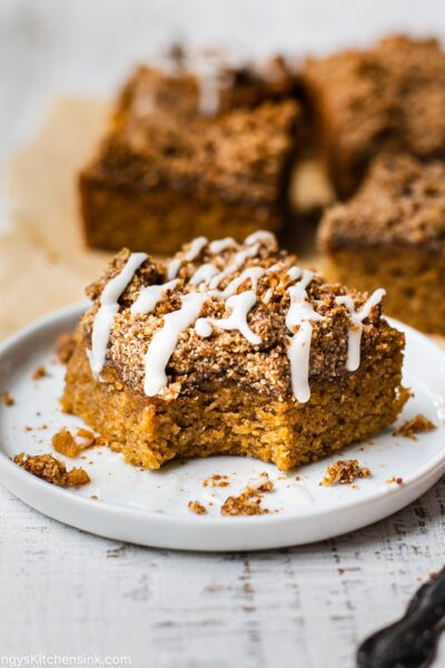 A piece of gluten-free cake with a paleo topping is drizzles with maple icing