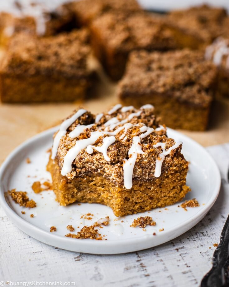 A piece of pumpkin coffee cake with a crumble topping drizzles with maple icing