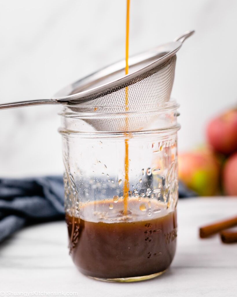 paleo fall spiced syrup is being poured into a jar through a strainer
