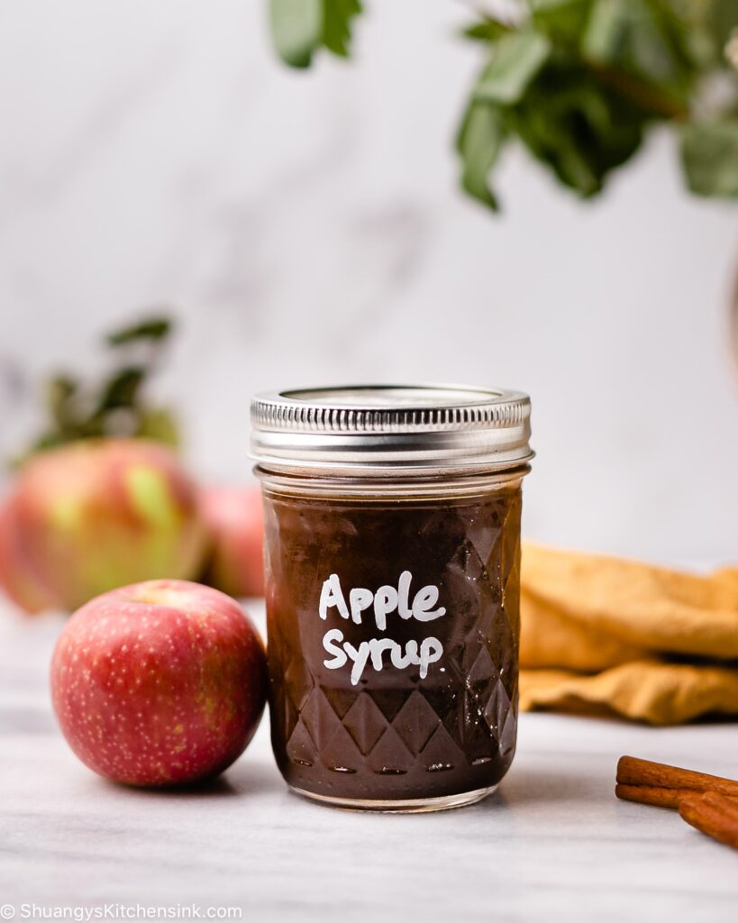 brown sugar apple syrup in a mason jar. there is a red honey crisp apple next to the har as well