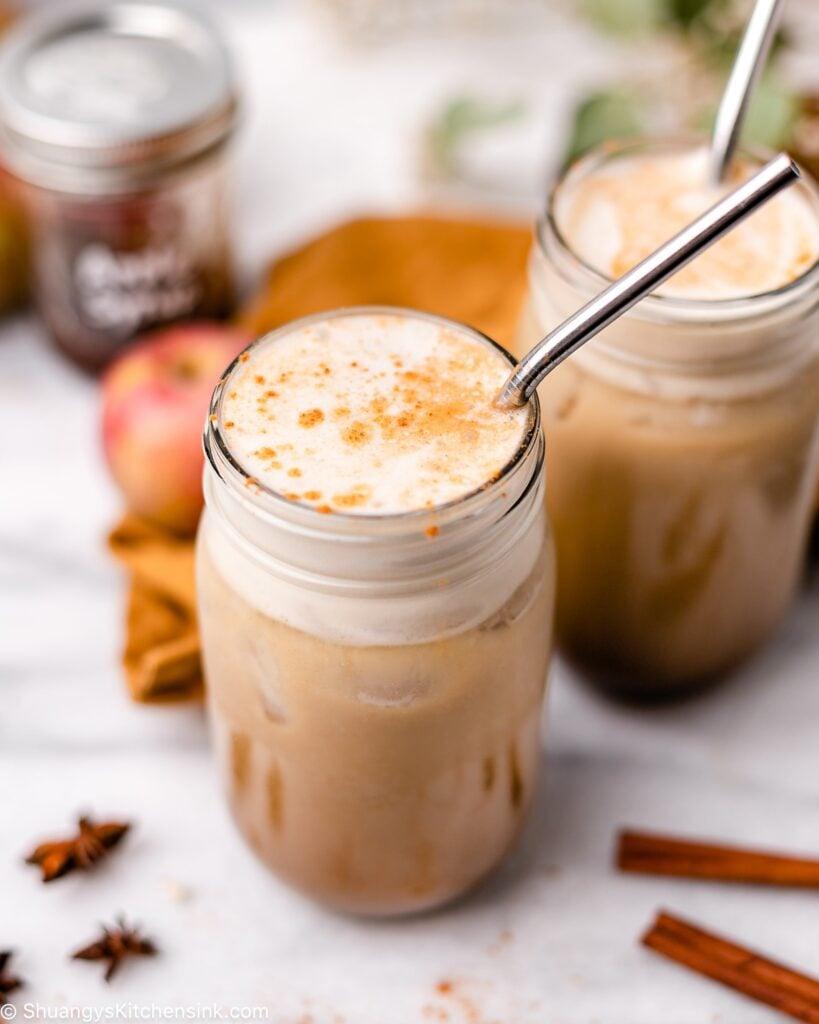 two homemade vegan Starbucks copycat apple crisp macchiato drinks on a fall decorated table