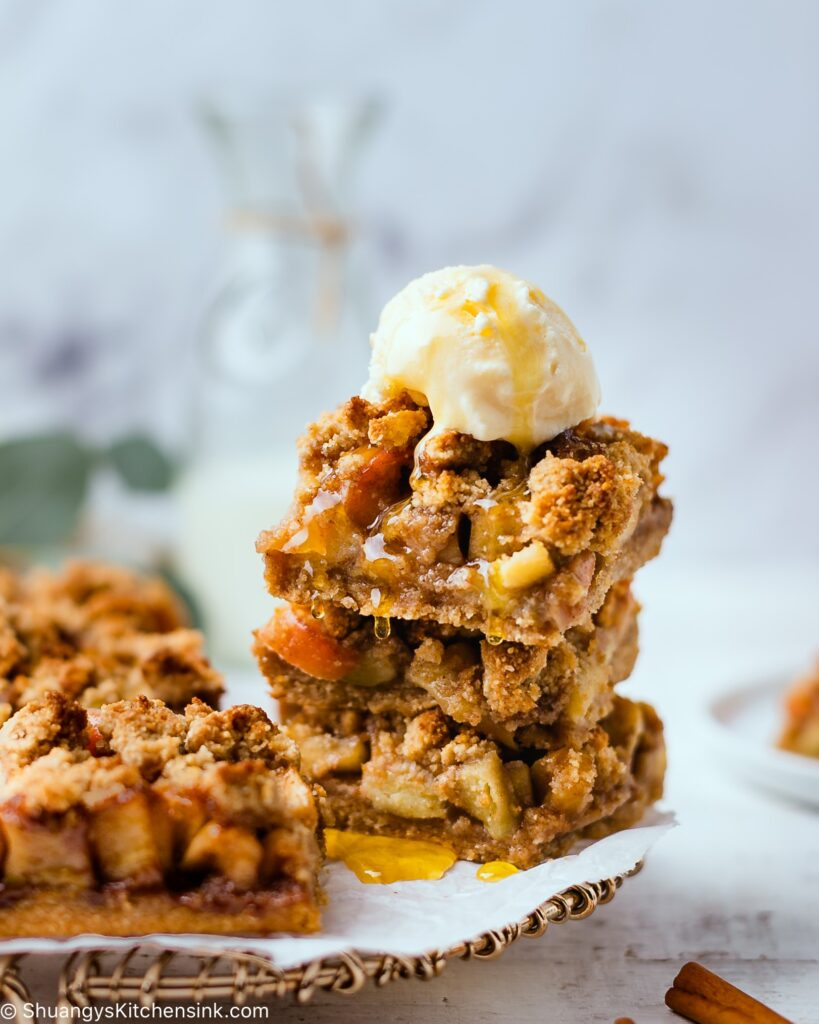 apple pie crumble bars stacked on top of each other with a dollop of vegan ice cream and maple syrup on top.
