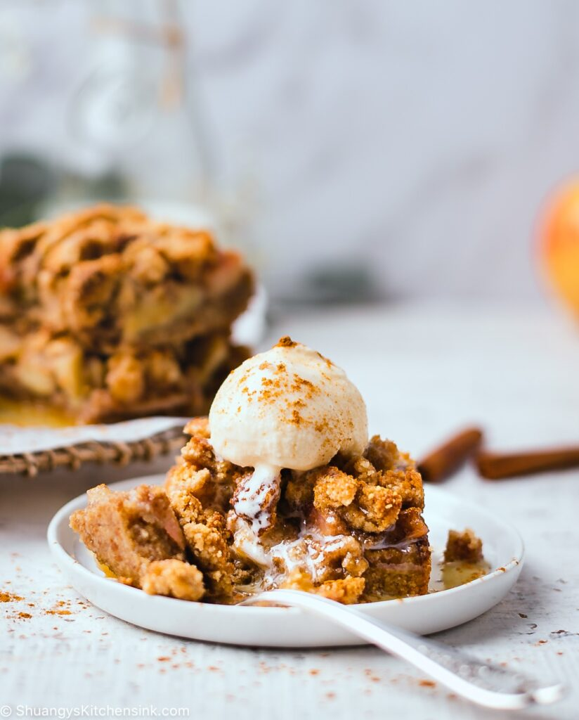 A gluten free apple pie crumble bar topped with vanilla ice cream that's dusted with cinnamon
