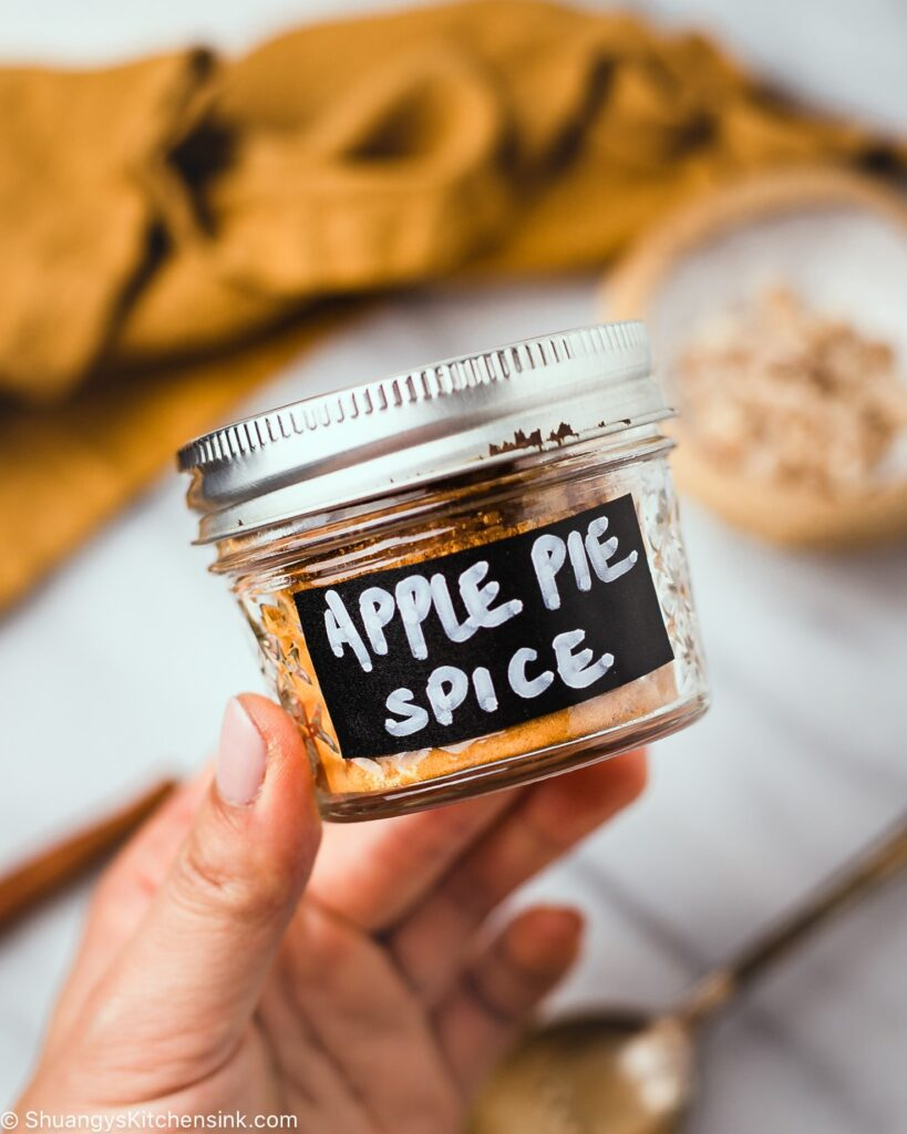 a hand is holding a small mason jar with homemade apple pie spice in it . It is labeled with a black an white hand written note