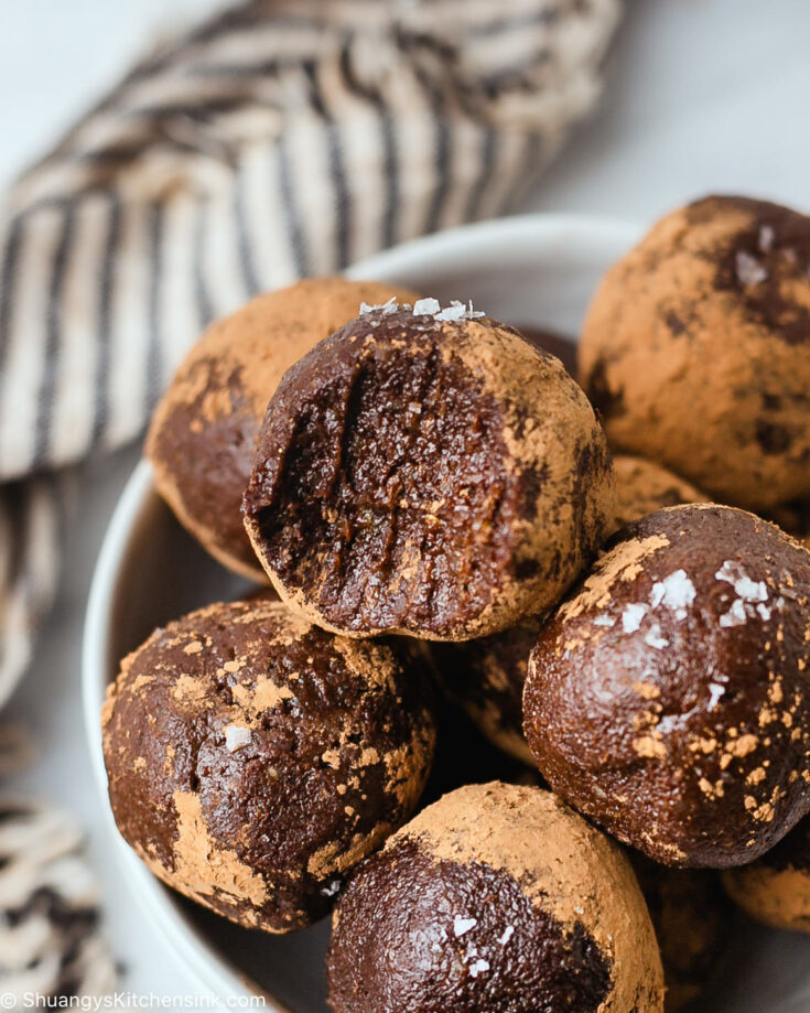 a bite is taken from a fudgy nut and chocolate ball topped with sea salt
