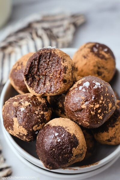 Raw vegan energy brownie alls that has been rolled in cacao powder