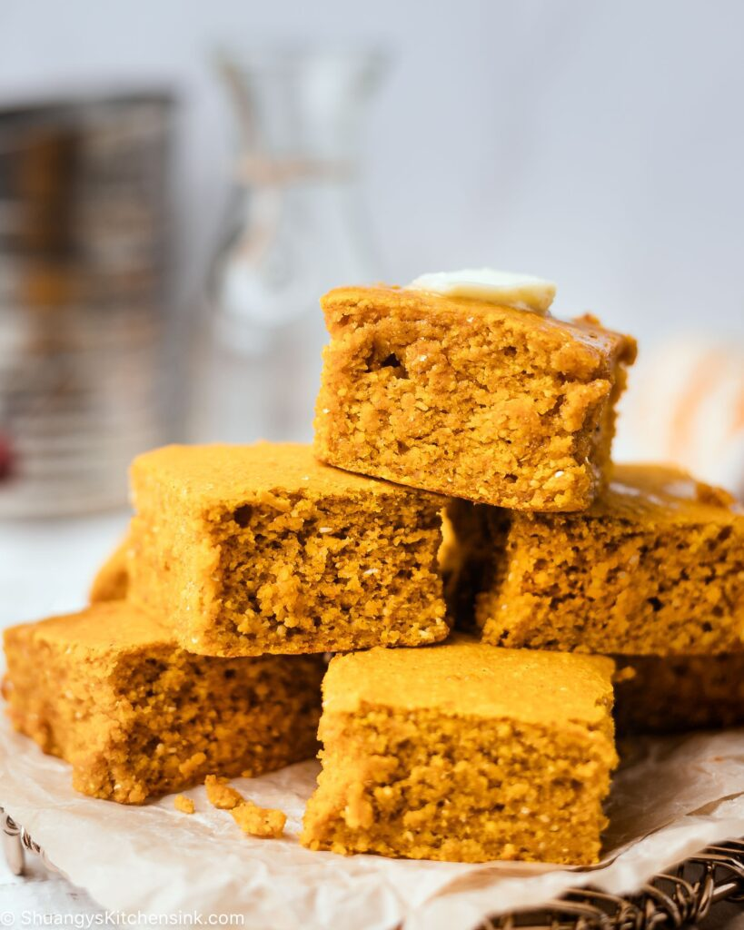 a pyramid of pumpkin cornbread squares. they are golden brown and looks moist and fluffy