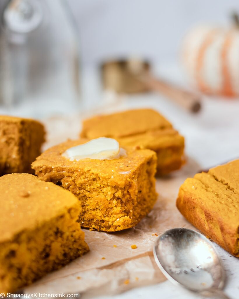 squares of soft and moist pumpkin cornbread that's gluten-free and dairy-free that's topped with honey butter